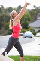 Active senior woman, in pink sports vest and leggings, warming up on driveway, stretching arms above head, smiling, profile