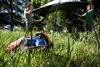 Young couple setting up tent on camping trip in woodland clearing, side view surface level