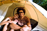 Young couple sitting in dome tent entrance on camping trip, woman leaning on manÔÇÖs shoulder, smiling, front view, portrait