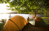 Young woman relaxing on camping trip near two dome tents beside lake at sunset, watching man standing on jetty in mid-distance, rear view lens flare