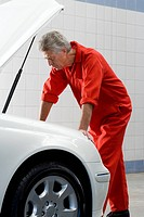 Mature male car mechanic, in red overalls, looking at car engine in auto repair shop, side view
