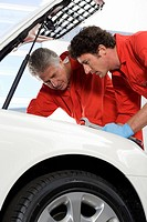 Two car mechanics, in red overalls and protective gloves, looking at car engine in auto repair shop, side view