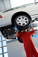 Male car mechanic, in red overalls and protective gloves, standing below car on hydraulic platform in auto repair shop, replacing wheel, face obscured...