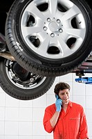 Male car mechanic, in red overalls and protective gloves, using mobile phone near hydraulic platform in auto repair shop, smiling