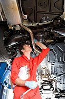 Male car mechanic, in red overalls and protective gloves, looking at underside of car on hydraulic platform in auto repair shop, holding wrench and cl...