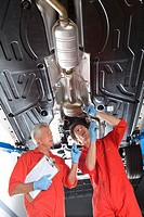 Two car mechanics, in red overalls and protective gloves, standing below car on hydraulic platform in auto repair shop, mature man holding clipboard, ...