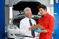 Car mechanic, in red overalls and protective gloves, talking to male customer beside car with open bonnet in auto repair shop, holding clipboard, smil...