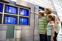 Mother and children looking at flight information screen in airport departure lounge, woman pointing, smiling