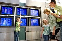 Family standing in airport departure lounge, excited boy 8-10 pointing to flight information screen, father looking on, mother and daughter looking at...