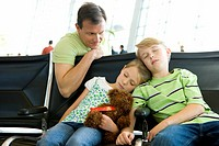 Father looking at children sleeping on seats in airport departure lounge, girl 7-9 holding soft toy