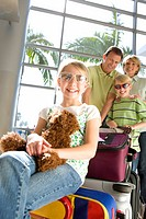 Family standing beside luggage trolley in airport, girl 7-9, in sunglasses, sitting on suitcase with soft toy in foreground, smiling, front view, port...