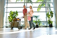Senior couple walking through airport, man pushing luggage trolley, smiling, side view surface level