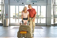 Senior couple entering airport through automatic doors, woman pushing luggage trolley, man with arm around woman, smiling, front view