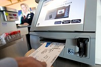 Traveller placing airline ticket into automatic check-in machine in airport, close-up, mid-section, rear view differential focus