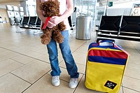 Girl 7-9 standing beside colourful, striped bag and empty seats in airport departure lounge, holding soft toy, low section, front view