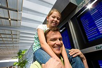 Father carrying daughter 7-9 on shoulders near flight information screens in airport departure lounge, smiling, low angle view