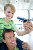 Father carrying son 8-10 on shoulders in airport, boy holding toy aeroplane, smiling differential focus