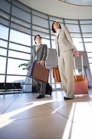 Businessman and woman walking with luggage in tow in airport, building entrance in background surface level