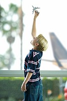 Blonde boy 8-10 playing with toy plane near large window in airport departure lounge, hand raised, profile