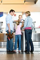Family checking in at airport check-in desk, female check-in attendant passing boarding passes to girl 7-9, smiling, rear view