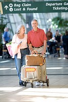 Senior couple pushing luggage trolley below ÔÇÿbag claimÔÇÖ and ÔÇÿlost and foundÔÇÖ sign, smiling