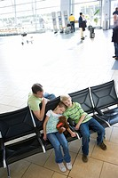 Father sitting beside children 7-10 in airport departure lounge, boy and girl sleeping, elevated view tilt
