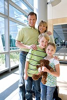 Family standing in airport, girl 7-9 holding teddy bear, smiling, front view, portrait
