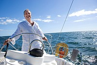 Mature man standing at helm of yacht out at sea, steering, smiling, front view