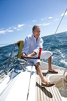 Mature man sitting on deck of yacht out at sea, adjusting rigging using rope pulley, smiling tilt