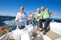 Two mature couples sailing out at sea, mature man standing at helm of yacht, steering, smiling, front view tilt