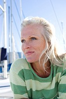Mature woman, in green striped jumper, sitting on deck of yacht moored at harbour jetty, smiling, close-up