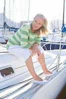 Mature woman, in green striped jumper, sitting on deck of yacht moored at harbour jetty, leaning forwards, smiling, side view, portrait
