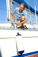 Mature man crouching on deck of yacht, untying mooring rope, smiling