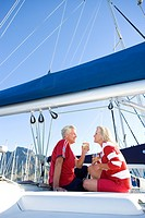 Mature couple, in red jumper and t-shirt, sitting on deck of yacht moored at harbour jetty, drinking white wine, smiling, profile