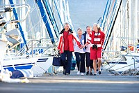 Two mature couples walking affectionately along harbour jetty past moored yachts, man carrying bag, smiling, front view