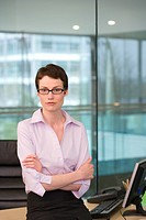 Businesswoman, with short hair and spectacles, leaning against desk in office, arms folded, portrait