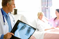 Mature male doctor holding x-ray, looking at nurse by mature female patient in hospital bed focus on doctor
