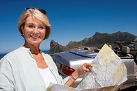 South Africa, Cape Town, mature woman holding map outdoors by car and sea, smiling, portrait, close-up