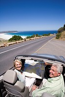 South Africa, Cape Town, senior couple with map parked on side of road by sea in convertible silver car, smiling, portrait, elevated view