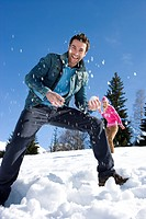 Young couple having snow fight in snow field, smiling, woman in background
