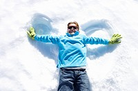 Boy 7-9 lying in snow making ´angel wings´, smiling, overhead view