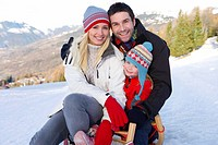 Young couple and daughter 6-8 embracing on sled in snow field, smiling, portrait, mountain range in background