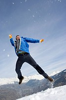 Young man in air in snow field, armsand legs outstretched, low angle view