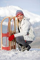 Young woman crouching by sled in snow field, smiling, portrait, mountain range in background