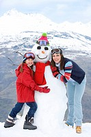 Mother and daughter 7-9 standing by snowman in snow, smiling, portrait, mountain range in background