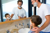 Father and son 6-8 shaving in bathroom, smiling