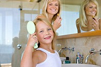 Mother and daughter 6-8 in bathroom, girl brushing hair, smiling, portrait