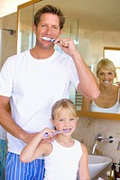 Couple and daughter 6-8 brushing their teeth in bathroom, smiling, portrait