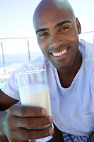 Young man holding glass of milk outdoors, smiling, portrait, close-up