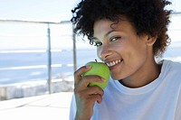 Young woman eating green apple outdoors, smiling, portrait, close-up